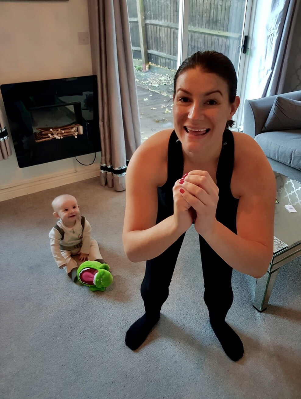 Mum doing squat next to baby